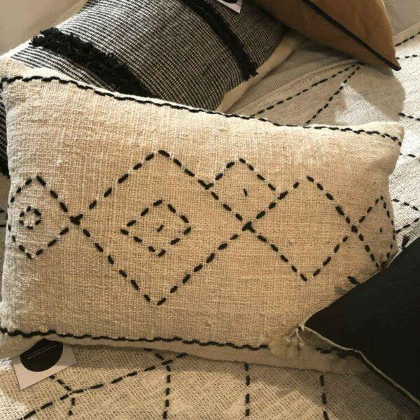 coussin écru brodé de fil de coton noir aux motifs tribaux style ethnique chic
